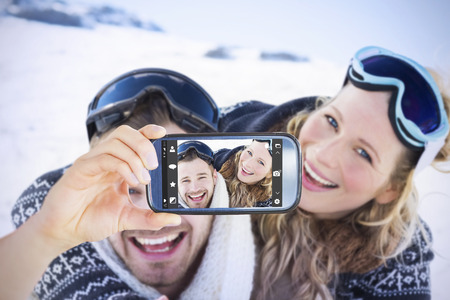 winter vacation: Hand holding smartphone showing against cheerful couple with ski goggles on snow Stock Photo