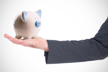 hand out: Businessman holding his hand out against piggy bank