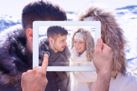 fur hood: Hand holding tablet pc against couple in fur hood jackets against snowed mountain Stock Photo
