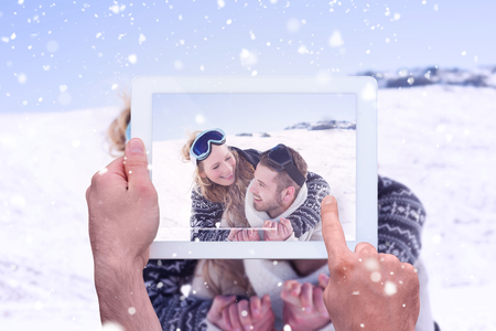 ski goggles: Hand holding tablet pc against close up of a cheerful couple with ski goggles on snow