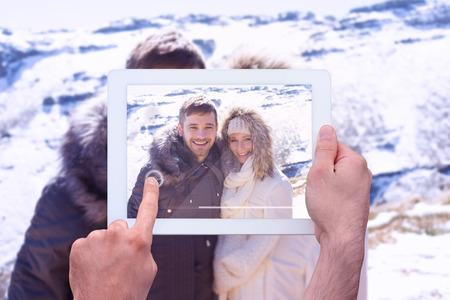 fur hood: Hand holding tablet pc against couple in fur hood jackets against snowed mountain range