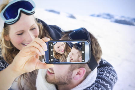 ski goggles: Hand holding smartphone showing against close up of a cheerful couple with ski goggles on snow Stock Photo