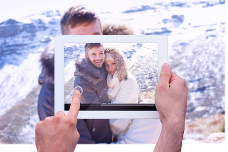 snowed: Hand holding tablet pc against couple in jackets embracing against snowed mountain