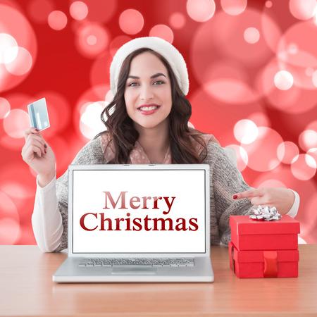 holiday spending: Festive brunette shopping online against digitally generated twinkling light design Stock Photo