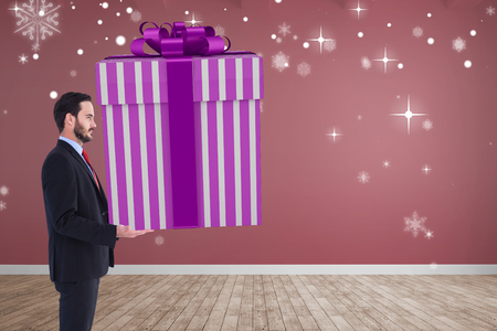 giant man: Stylish man with giant gift against room with wooden floor Stock Photo