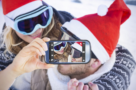 ski goggles: Hand holding smartphone showing against close up of a cheerful couple in ski goggles on snow Stock Photo