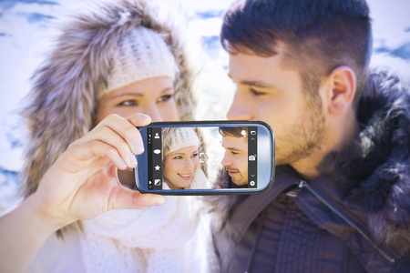 snowed: Hand holding smartphone showing against couple in fur hood jackets against snowed mountain Stock Photo