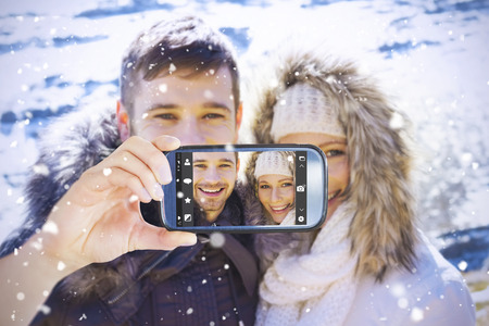 fur hood: Hand holding smartphone showing against couple in fur hood jackets against snowed mountain range Stock Photo