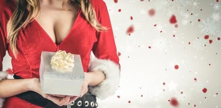 pere noel sexy: Sexy Santa fille tenant cadeau contre motif de flocon de neige Banque d'images