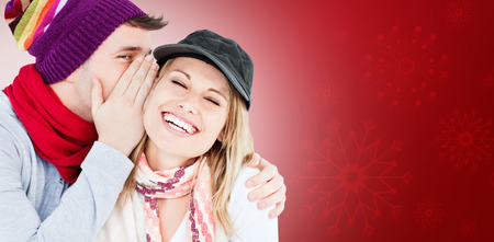 Young couple sharing a secret against red snowflake background photo