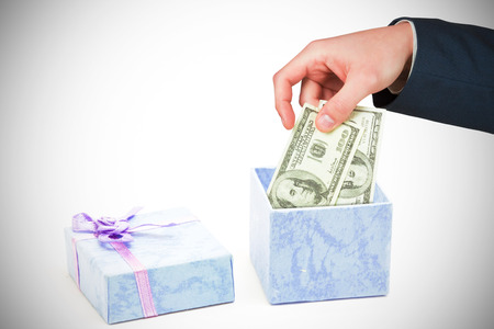 blue gift box: Hand holding hundred dollar bills against open blue gift box with purple ribbon