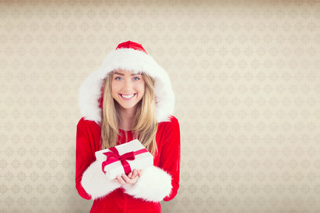 sexy santa girl: Sexy santa girl holding gift against room with wooden floor Stock Photo