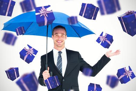 sheltering: Businessman sheltering under black umbrella against purple presents
