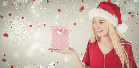 gift bag: Festive blonde holding a gift bag against snowflake pattern