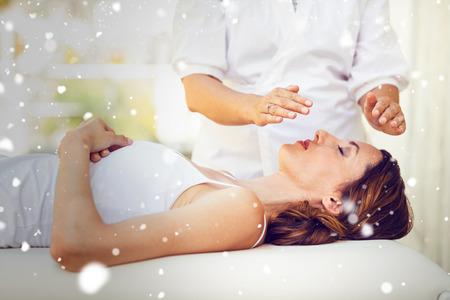 Snow against calm woman receiving reiki treatment 版權商用圖片