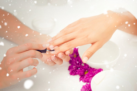 cosmetician: Snow against beautician applying nail varnish to female clients nails