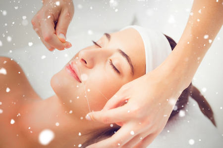 threading: Snow against hands threading beautiful womans upper lip Stock Photo