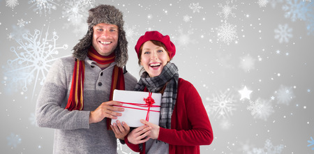 Couple smiling and holding gift against snowflake pattern