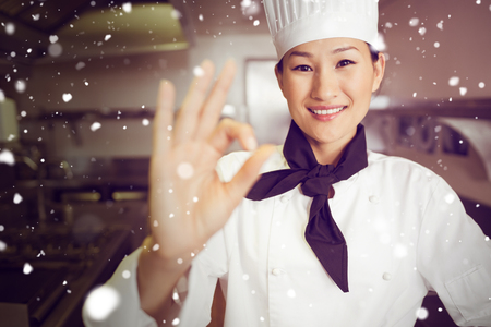 okay: Snow against smiling female cook gesturing okay sign in kitchen Stock Photo