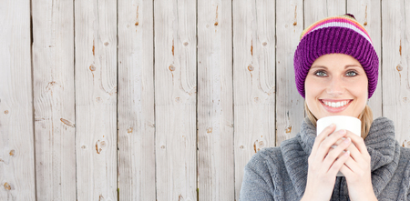 mirthful: Smiling woman in a grey pullover against white background against wooden background Stock Photo
