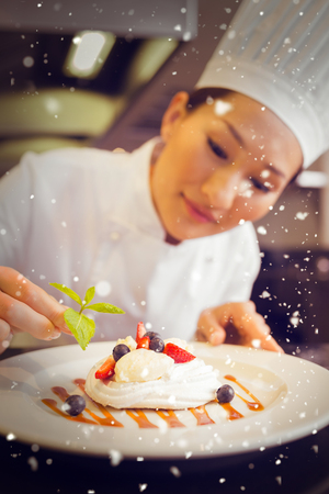 garnishing: Snow against concentrated female chef garnishing food Stock Photo