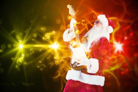 papa noel: Santa que juega la guitarra el�ctrica de color naranja contra fondo brillante abstracto negro
