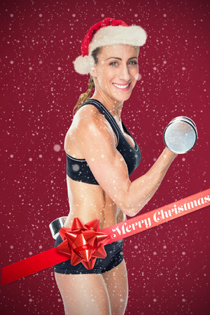 lean out: Female bodybuilder working out with large dumbbells smiling at camera against red background Stock Photo