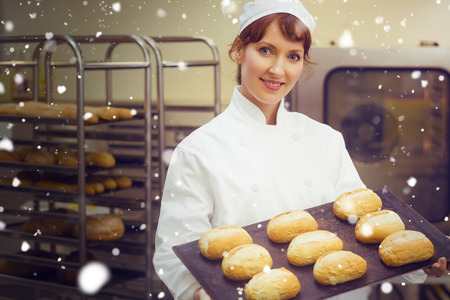 baking tray: Snow against happy female baker showing some rolls on a baking tray