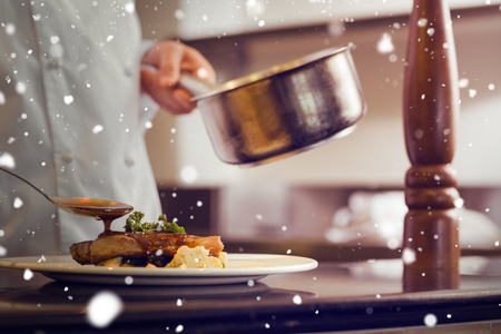 chef: Snow against closeup mid section of a chef garnishing food Stock Photo