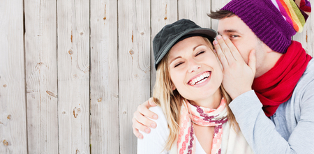 Young couple sharing a secret against wooden background photo