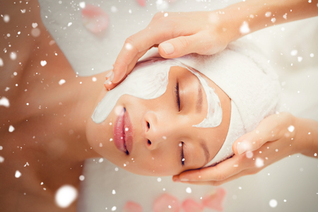spa therapy: Snow against hands massaging womans face at beauty spa Stock Photo
