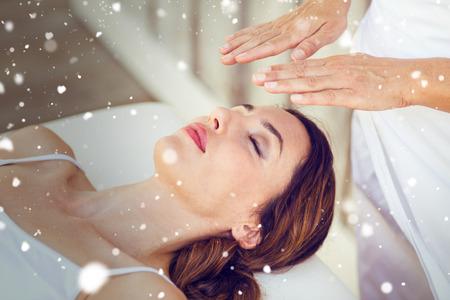 reiki: Snow against calm woman receiving reiki treatment Stock Photo