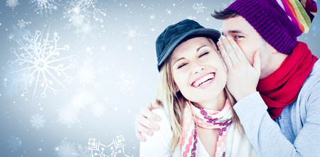 Young couple sharing a secret against snowflake pattern photo