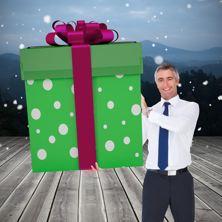 giant man: Stylish man with giant gift against wooden planks against mountains Stock Photo