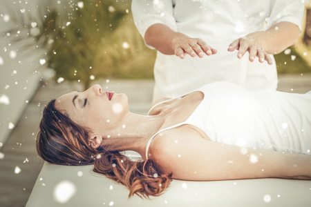 healing hands: Snow against calm woman receiving reiki treatment Stock Photo