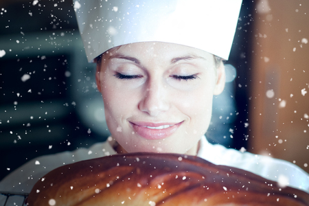 Snow falling against radiant female chef baking bread