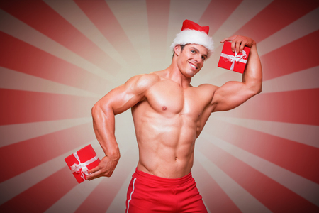 sexy pose: Shirtless macho man in santa hat holding gifts against linear design