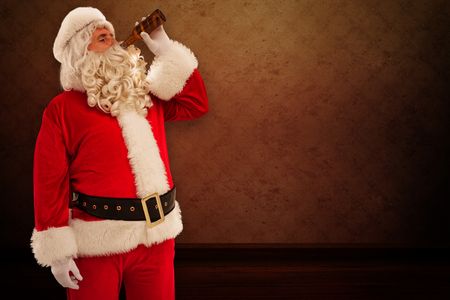 christmas wallpaper: Father christmas drinking a beer against room with wallpaper Stock Photo