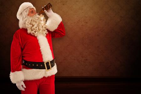 hombre tomando cerveza: Padre Navidad que bebe una cerveza contra el cuarto con el papel pintado Foto de archivo