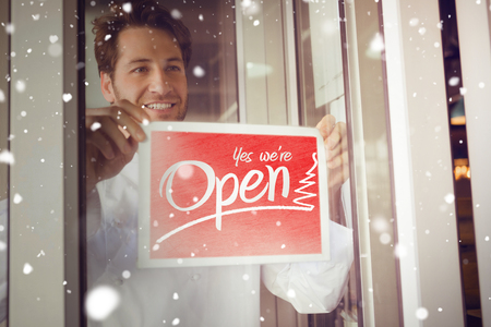 open sign: Snow against cafe owner showing open sign Stock Photo