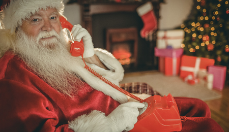 on call: Smiling santa making a phone call at home in the living room