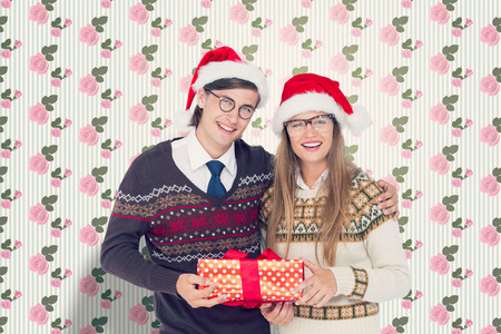 kitsch: Geeky hipster couple holding present  against kitsch floral pattern wallpaper with roses