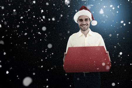 wearing santa hat: Happy man wearing Santa hat while holding red gift against snow Stock Photo