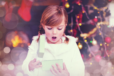 shocked: Glowing background against shocked little girl opening a gift