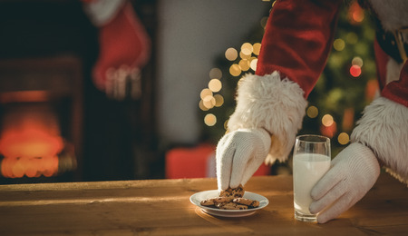 glass of milk: Santa claus picking cookie and glass of milk on the table at home