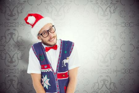 patterned wallpaper: Geeky hipster in santa hat against elegant patterned wallpaper in grey tones Stock Photo