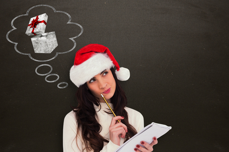 Festive brunette thinking about her christmas list against blackboard