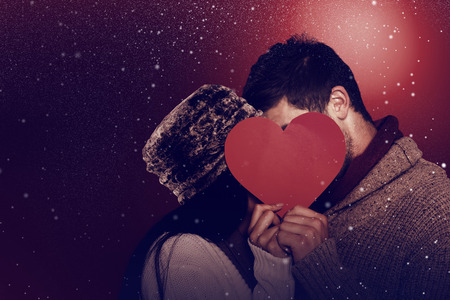 personas abrazadas: Young couple kissing behind red heart against snow