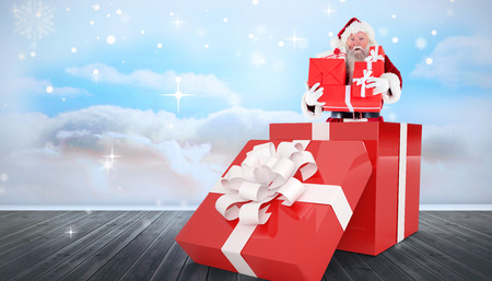 floorboards: Santa standing in large gift against clouds in a room