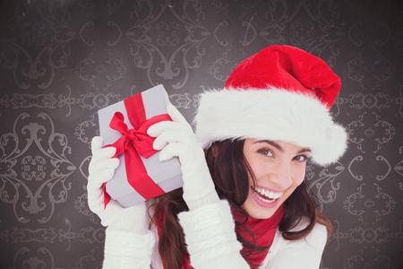 patterned wallpaper: Happy brunette in santa hat holding gift against elegant patterned wallpaper in grey